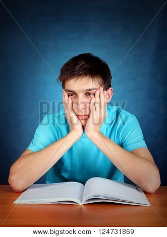 Sorrowful Student at the School Desk on the Blue Background