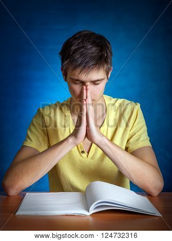 Young Man praying on the Blue Background