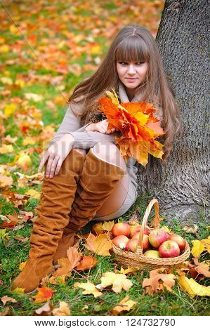 Portrait of beautiful young woman with autumn leaves