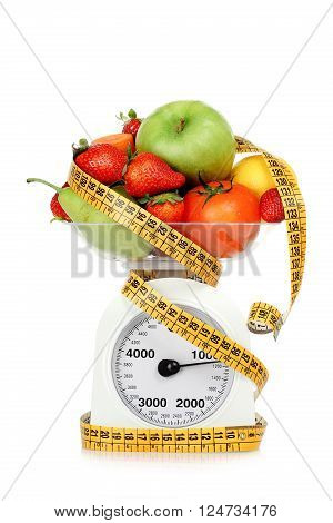 measuring tape around scales with fruits and vegetables dieting concept