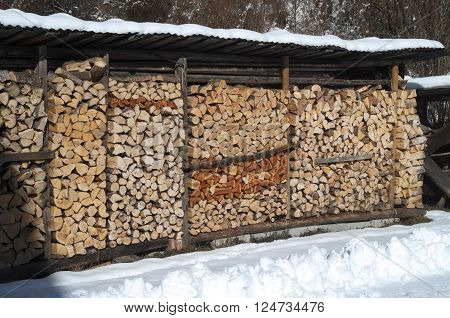 Pile of chopped wood ready for the fireplace with snow