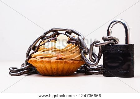 Diet sugar sweet food addiction concept. Cake cupcake wrapped in metal chain and padlock