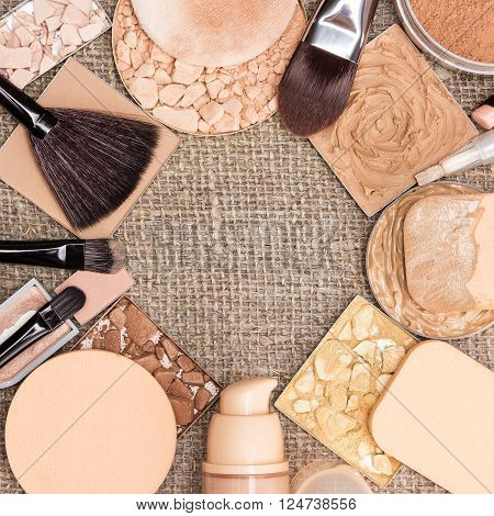 Beauty background. Makeup products to even out skin tone and create the perfect complexion laid out as frame on sackcloth. Foundation, concealers, various types of powder. Copy space in the center