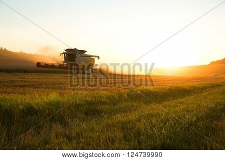 A field getting harvested by a agricultural machine.