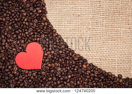 Bunch of coffee beans with red paper heart and gunny textile