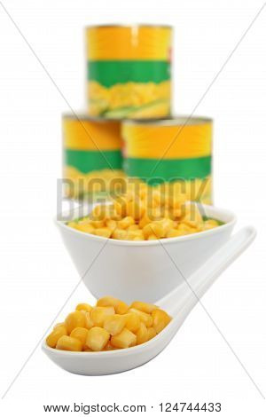 Canned sweet corn in cans, bowl and spoon, focuse on spoon, isolated on white background