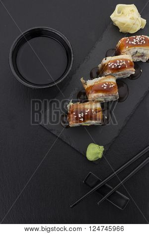 Eel Sushi Roll On A Plate With Ginger Wasabi Soy Sauce And Chopsticks Over Black Background