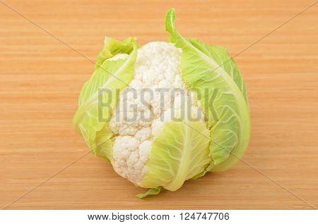 Whole ripe cauliflower isolated on wooden background