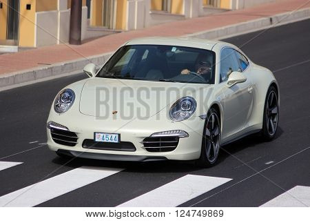 Monte-Carlo Monaco - April 6 2016: Porsche 911 Carrera S on Avenue d'Ostende in Monaco. Man Driving an Expensive White Porsche 911 50th anniversary edition in the south of France