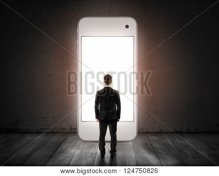 Back view of businessman standing opposite big sized smartphone with glowing screen. IPhone. Concept.