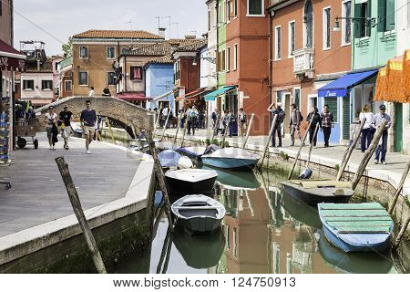 BURANO VENICE ITALY - APRIL 24 2015: Tourist people walking around canal with colorful houses in beautiful city of Burano. Burano is an island in the Venetian Lagoon northern Italy.