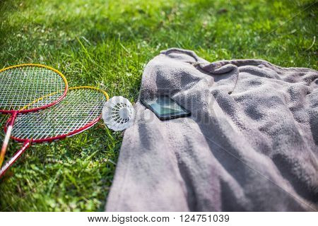 Shuttlecock and badminton racket mobilephone and Blue picnic blanket on the grass field
