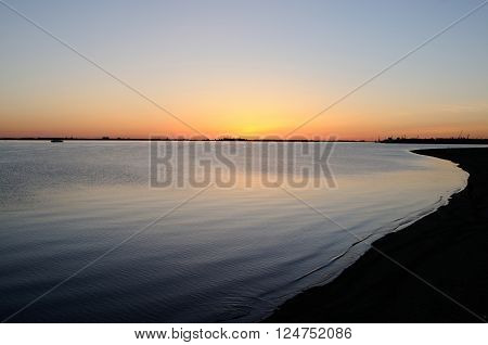 Reflection of the sunset in calm waters of a lowland river (Northern Dvina), Arkhangelsk, Russia