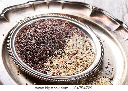 Metal plate with mixed raw quinoa, South American grain on white rustic wooden background. Healthy and gluten free food. Copy space.