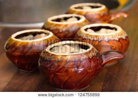 Ceramic pots for roasting on a kitchen table. A close up in pots the meat pieces which are filled in with cheese and sour cream sauce are visible