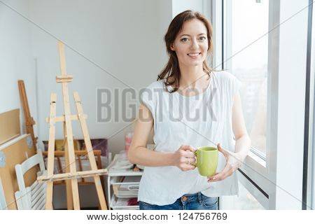 Cheerful beautiful woman painter drinking tea near the window in art studio