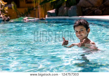 Young boy kid child eight years old having fun in swimming pool leisure activity thumbs up