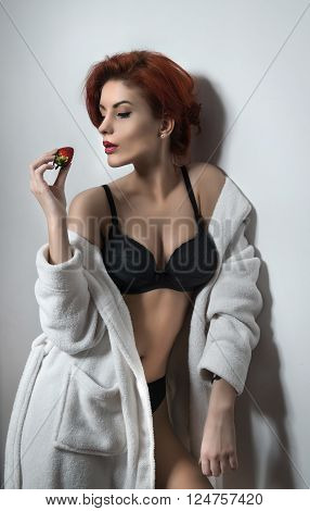 Attractive woman with short red hair in white towel rob over black lingerie holding a strawberry. Side view of perfect body woman in lingerie against white wall. Classic boudoir shot. Erotic photo.