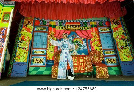 LAMPANG, THAILAND - FEBRUARY 18, 2016: Colorful stage of chinese theater and one actor playing a role in a traditional dramatic play on February 18, 2016. Population of Lampang is near 59000 people