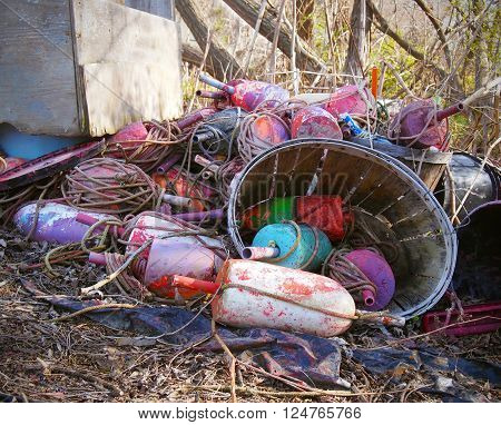 A pile of old buoys and tangled ropes with a bushel in the sticks.