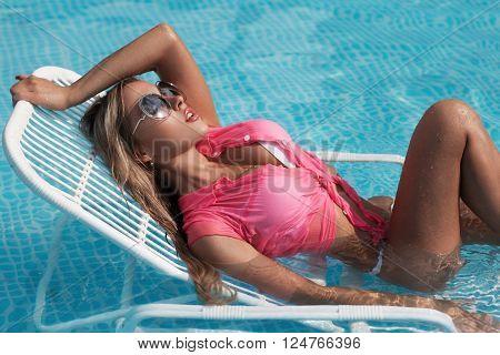 sexy girl in bikini sunbathing at the pool