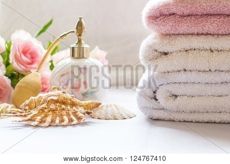 Bath arrangement with parfume bottle folded towels and pink roses