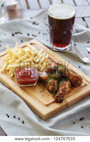 chicken drumsticks and french fries on a wooden board