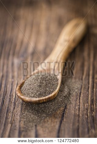 Portion of milled Black Pepper (close-up shot; selective focus) on wooden background