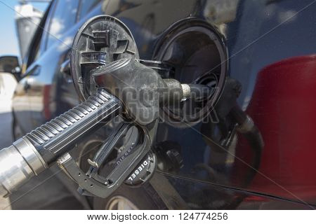 Car refueling on a petrol station. Nozzle detail