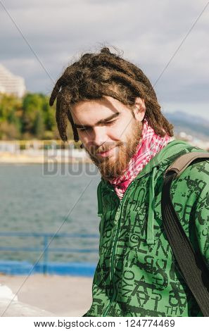 Outdoor portrait of young man with dreadlocks