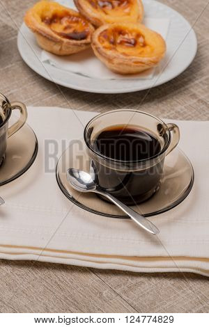 Pasteis de Nata or Portuguese Custard Tarts with black coffee on wooden table.