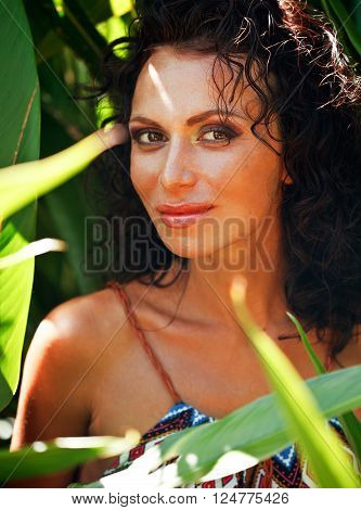 middle aged brunette elegant woman with green leaf in exotic jungle close up smiling face, lifestyle people concept, nude makeup