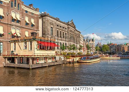 AMSTERDAM, NETHERLANDS - JULY 07, 2015: Cruise boats on canal in Amsterdam - capital city, most populous in Netherlands and popular tourist destination with more than 5 million visitors annually.