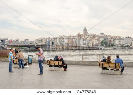 Istanbul Turkey - Jun 28 2015: In early morning many people women and men were sitting or just standing before Bosphorus Strait Galata Bridge and Beyoglu area.
