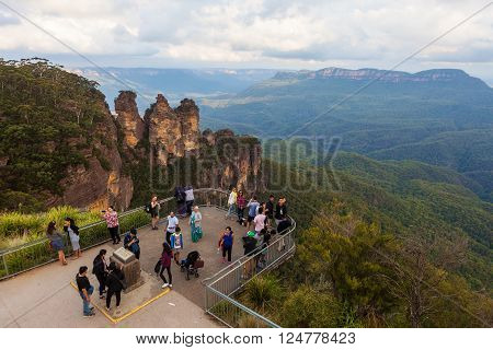 KATOOMBA, AUSTRALIA - MAR 27 2016:Tourists enjoying the view of the famous Three Sisters rock formation from Echo Point Lookout. Katoomba, New South Wales, Australia