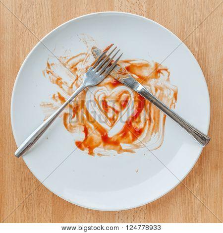 Knife and fork crossed in finish plate and heart shape ketchup concept of tasty.