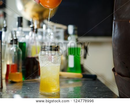 Bartender is straining cocktail in a glass