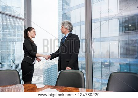 Mature business man shaking hand young business woman