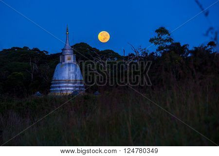 Buddhist temple and full moon in down at jungle Sri Lanka