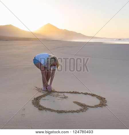 Woman drawing heart in sand on beautiful solitary Cofete beach in sunset. Love, travel concept. Fuerteventura, Canary Islands, Spain.