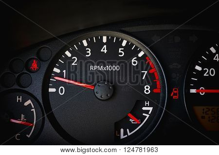 Dashboard of a car showing tachometer partial speedometer temperature gauge battery gauge seat belt warning light and open door warning light