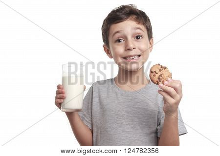 Little boy eating chocolate chip cookie and milk