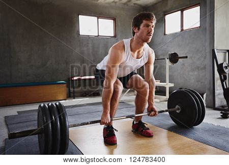 Wide angle image of a serious young man about to lift some heavy weights in a private gym