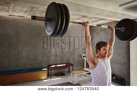Wide angle shot of a strong man lifting very heavy training weights in a private gym