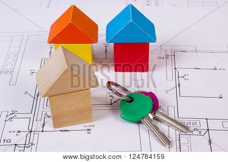 Houses shape made of wooden blocks and home keys lying on electrical construction drawings of house concept of building house drawing for projects