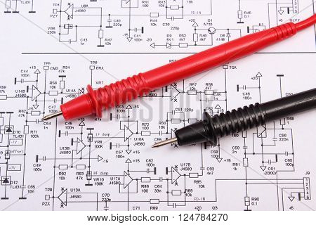 Cable of multimeter on diagram of electronics printed circuit board, drawing and tools for engineer jobs