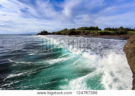 Silhouette of Tahah Lot Temple and ocean waves at sunny day, Bali, Indonesia