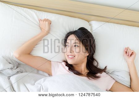 Young woman waking up in bed and stretching her arms