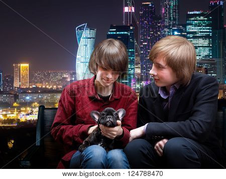 Teenagers sitting on a bench with a dog in their arms. Guy and girl date. Night, night city, skyscrapers.
