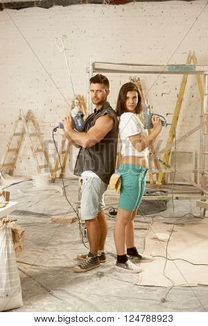 Determined young couple looking serious holding power drill, renewing home.